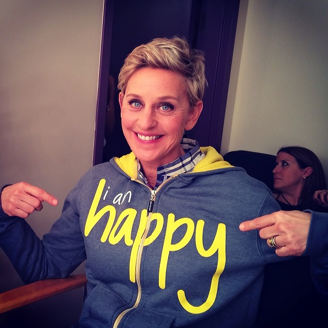 "Ellen DeGeneres, wearing ""I'm Happy"" Hoodie from Peace Love World"